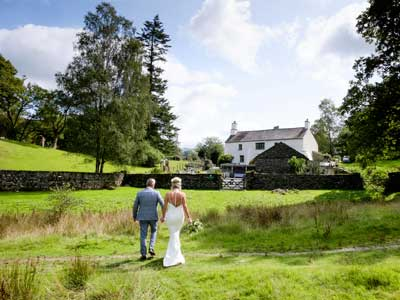 A bride and groom walking back from the lake to the wedding reception at Cote How in Rydal