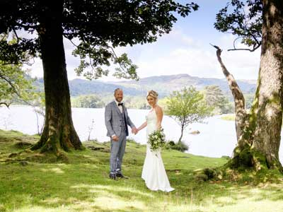 Bride and Groom hand in hand on the lake shores of Rydal Water after having their legal wedding ceremony at Cote How in Rydal