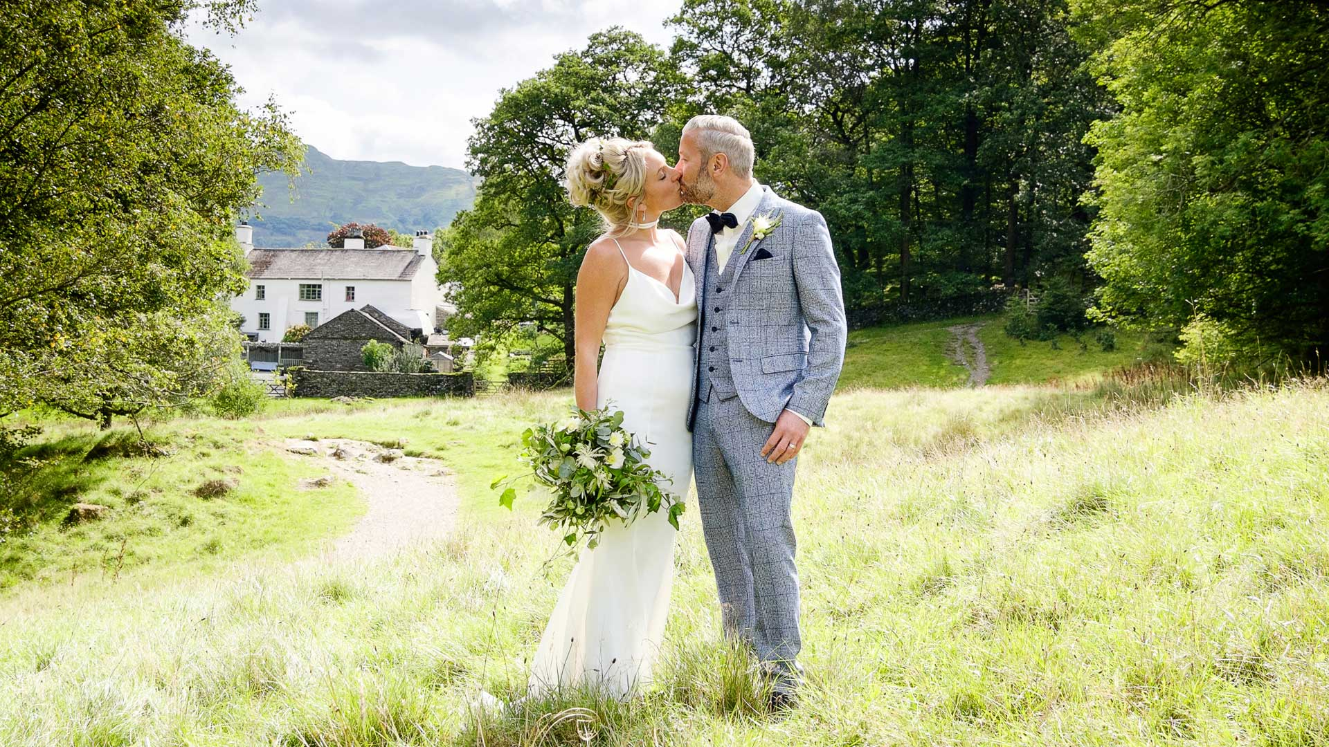 Bride and Groom kissing in the flower meadow opposite Cote How and Rydal Water