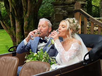 Bride and Groom sipping Prosecco in the back of a vintage Austin 7