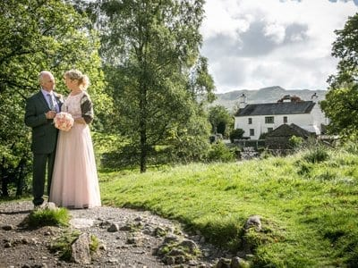 Mature Wedding Couple standing in Flower Meadow at Rydal Water after eloping to the Lake District