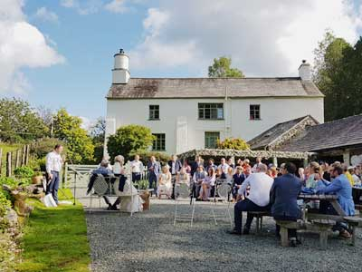 Evening Wedding Reception as guests sit around for the speeches Al Fresco in the evening sunshine outside the barn