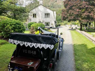 Just Married garland hangs on the back of a vintage Austin 7 as it waits to take the Bride and Groom on their way at Cote How in the Lake District