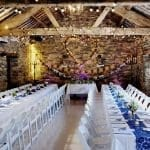 Tables dressed in white linen with blue lace for the Wedding Breakfast Set up in the ancient barn at Cote How
