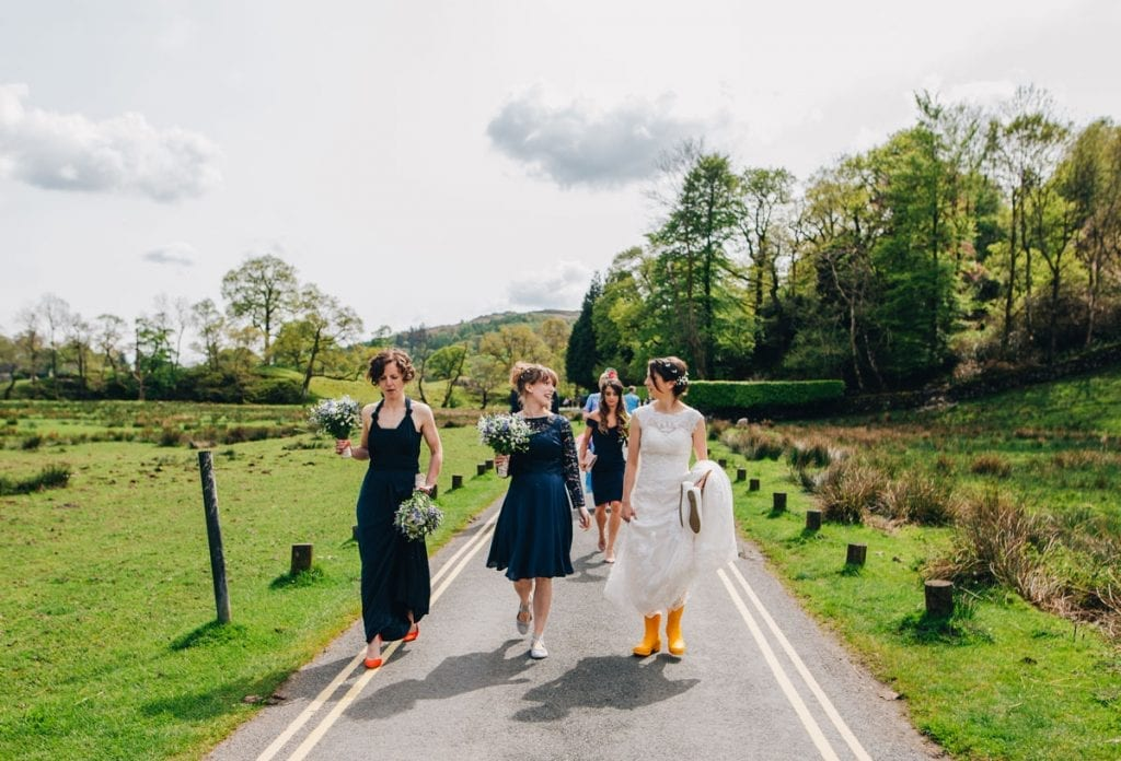 Bride in yellow wellies walking to her own wedding