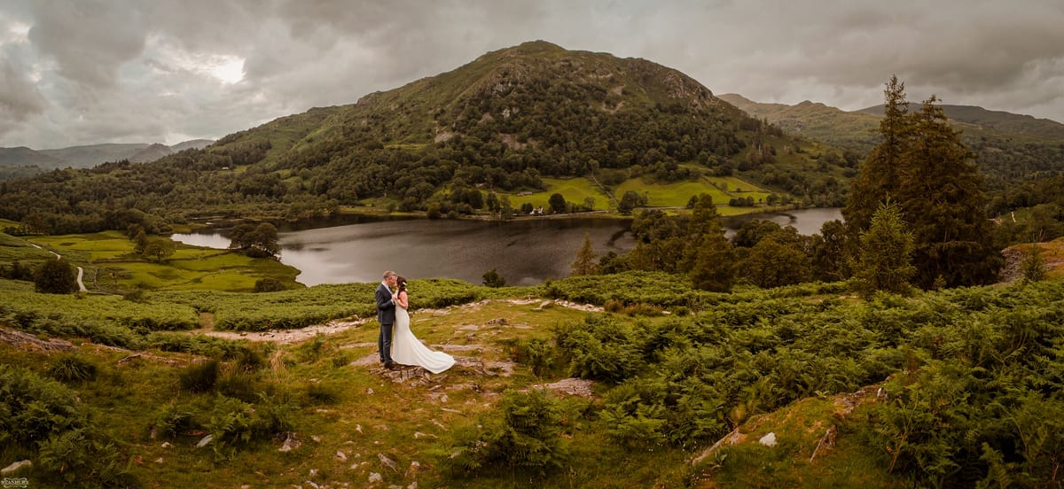 Bride-and-Groom-standing-by-Rydal-Caves-overlooking-Rydal-Water-at-Cote-How-Lake-District-Weddings