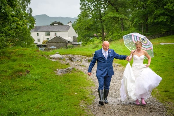 Bride and Groom with umbrella in rain at Rydal Water in the Lakes