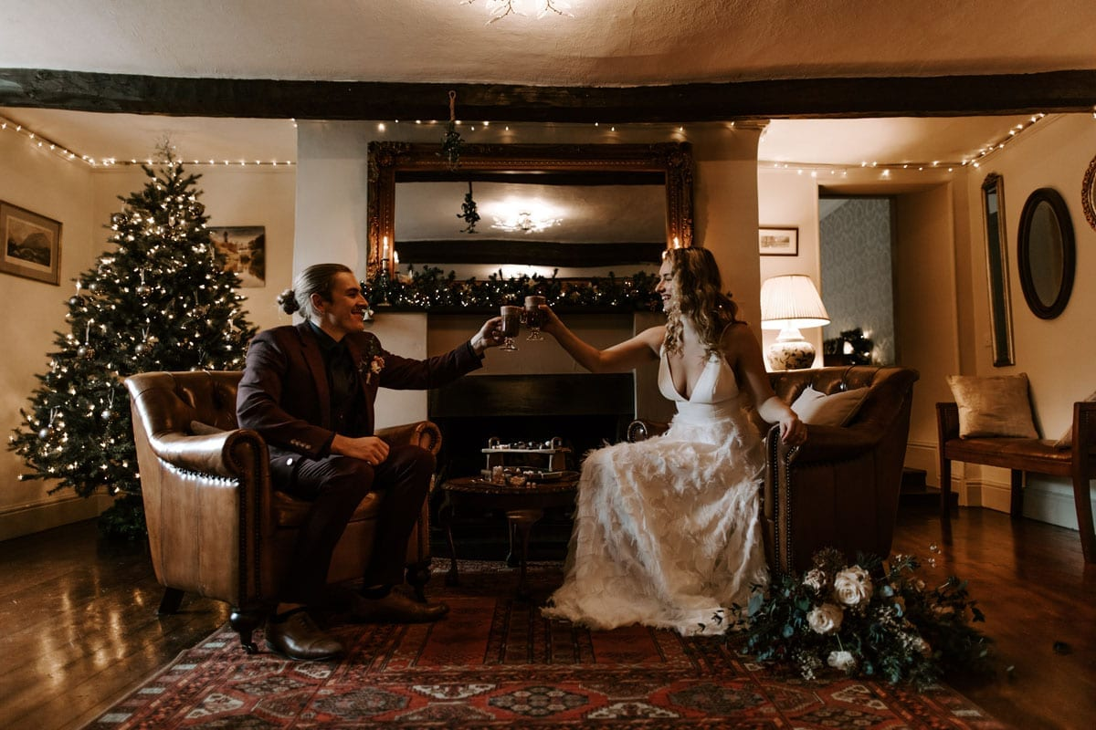 Couple-Celebrating-with-Hot-Chocolate-by-the-Log-Fire-and-Christmas-Tree
