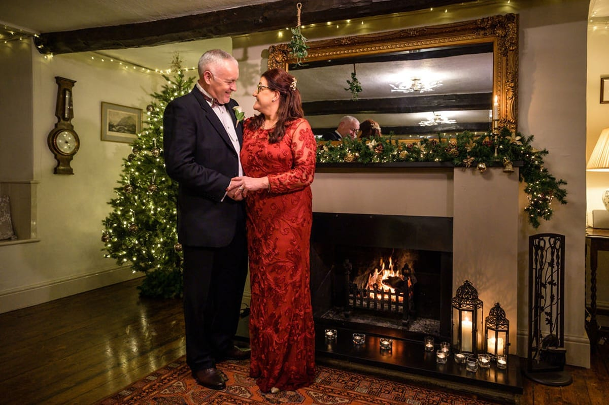 Bride-and-Groom-with-Chritmas-Tree-and-Hearth---Just-Married-after-their-Elopement-wedding-in-the-Lake-District