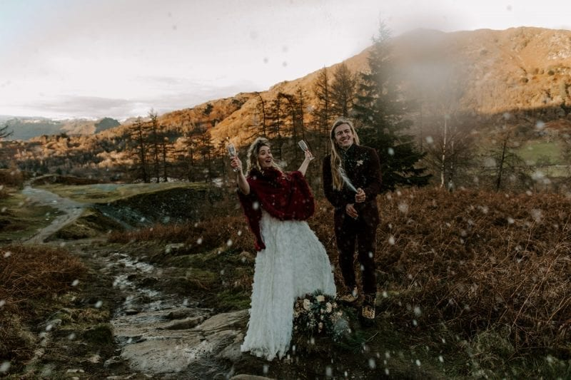 Bride and Groom on a mountain popping Prosecco to celebrate their adventure elopement at Cote How Lake District Weddings