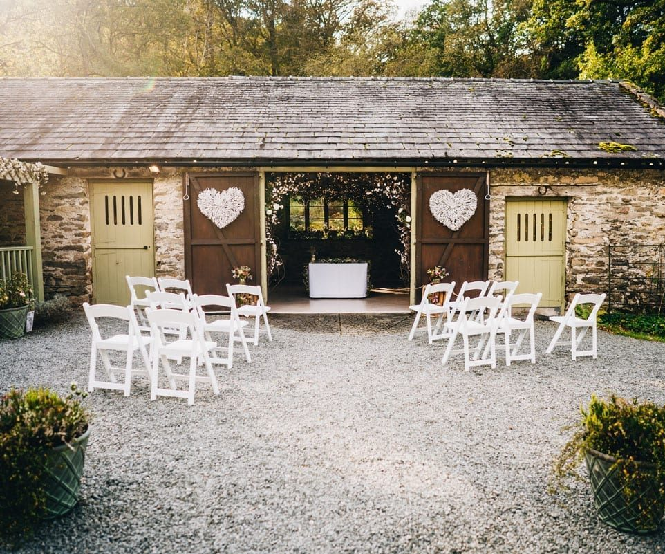 Outdoor Lake District Barn Wedding Ceremony set up with white chairs