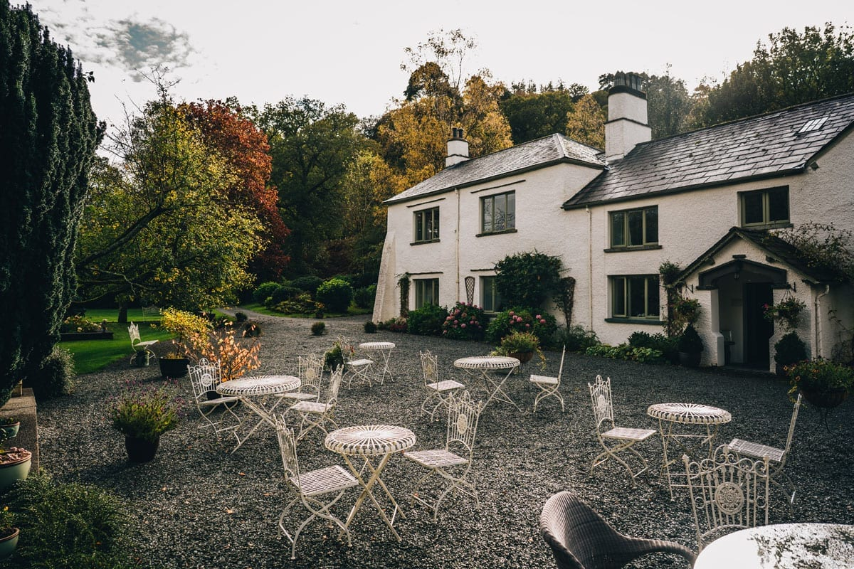 White Lake District Farmhouse Wedding Venue with outdoor wrought iron tables and chairs for drinks reception