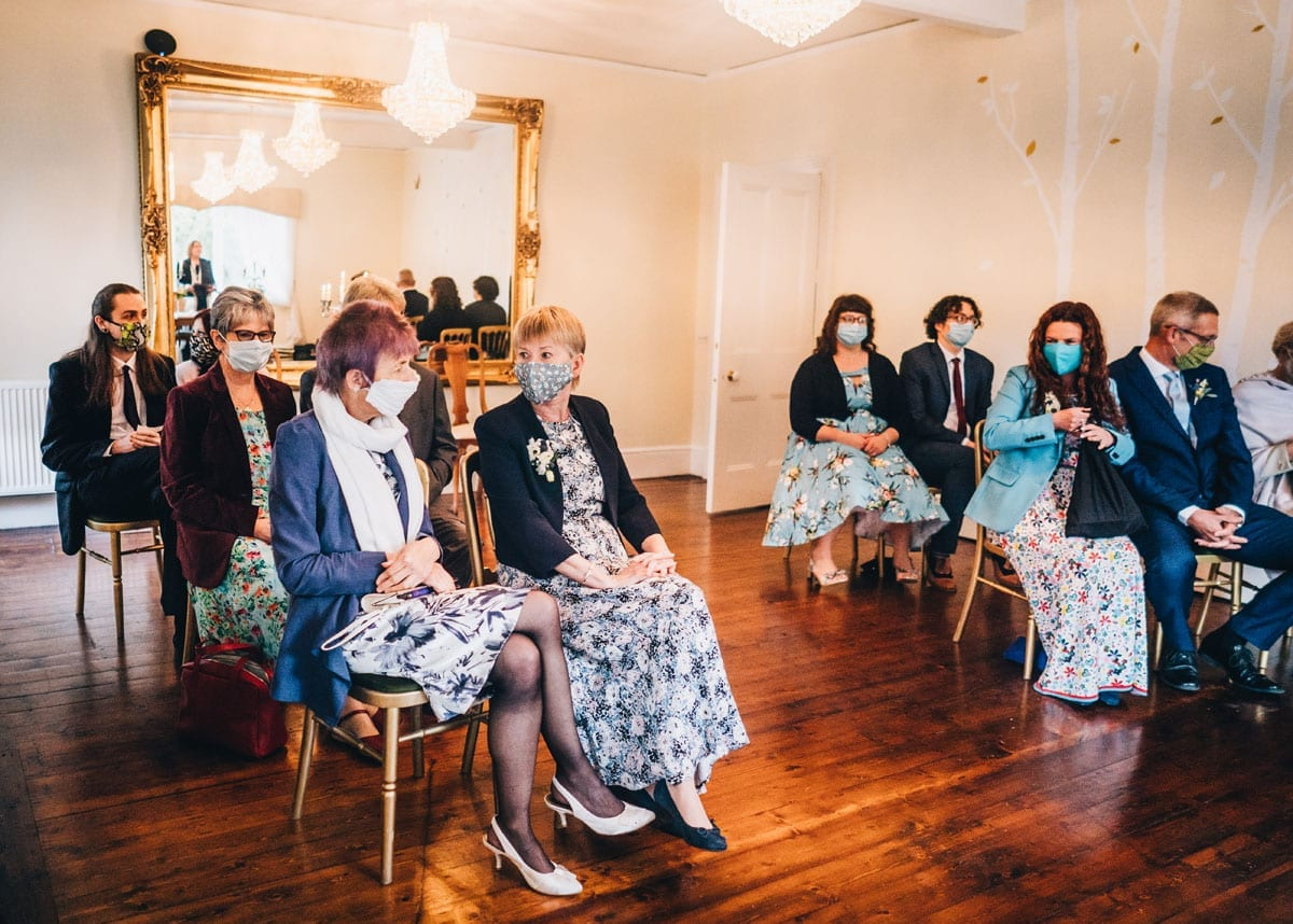 Guests seated at a Covid Secure Wedding Venue wearing face masks and socially distant