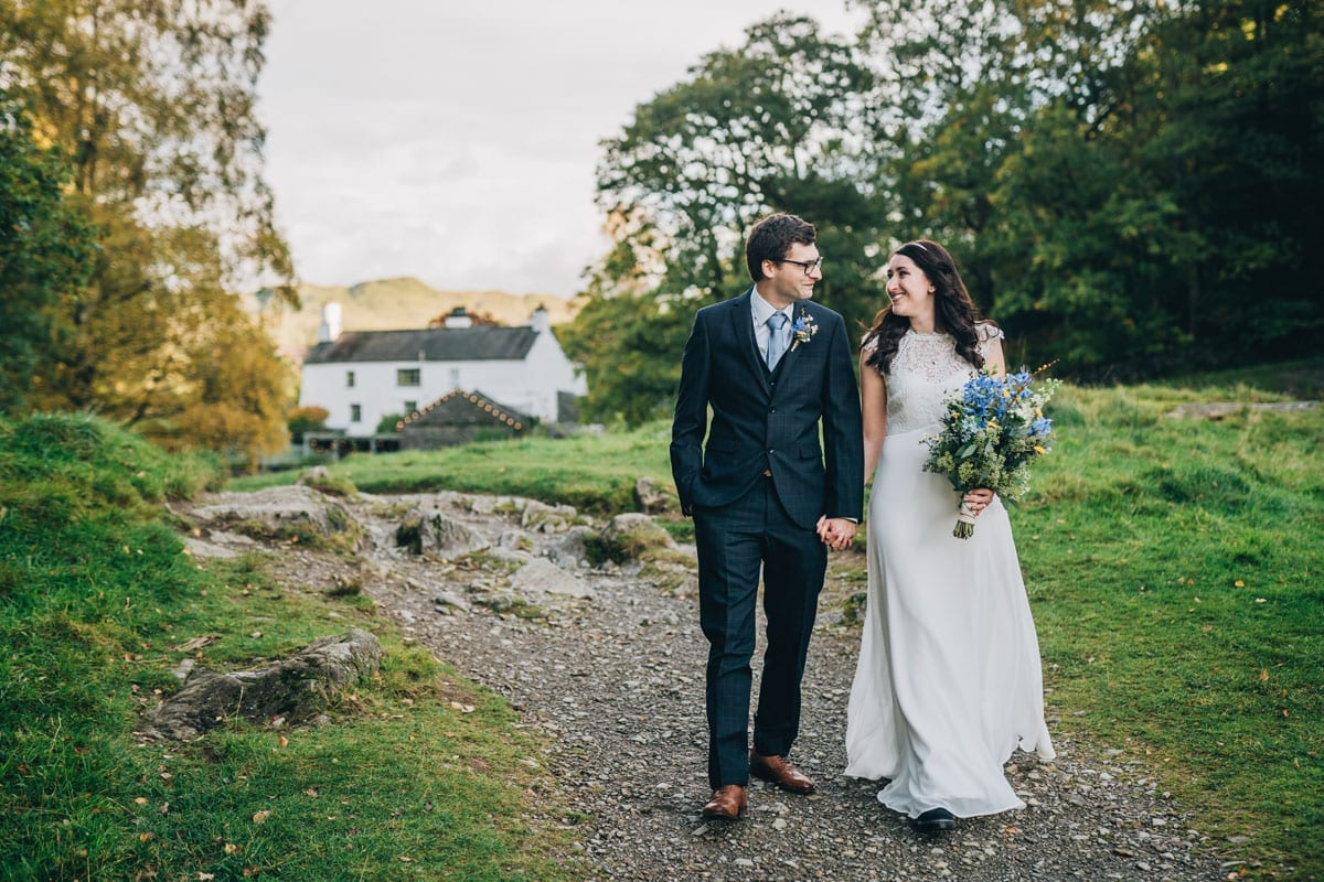 Groom and Bride strolling to the lake side of Rydal Water from their wedding venue - Cote How in the Lake District