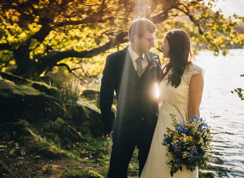 Bride and Groom in soft evening light by the lake side of Rydal Water after their wedding ceremony at Cote How