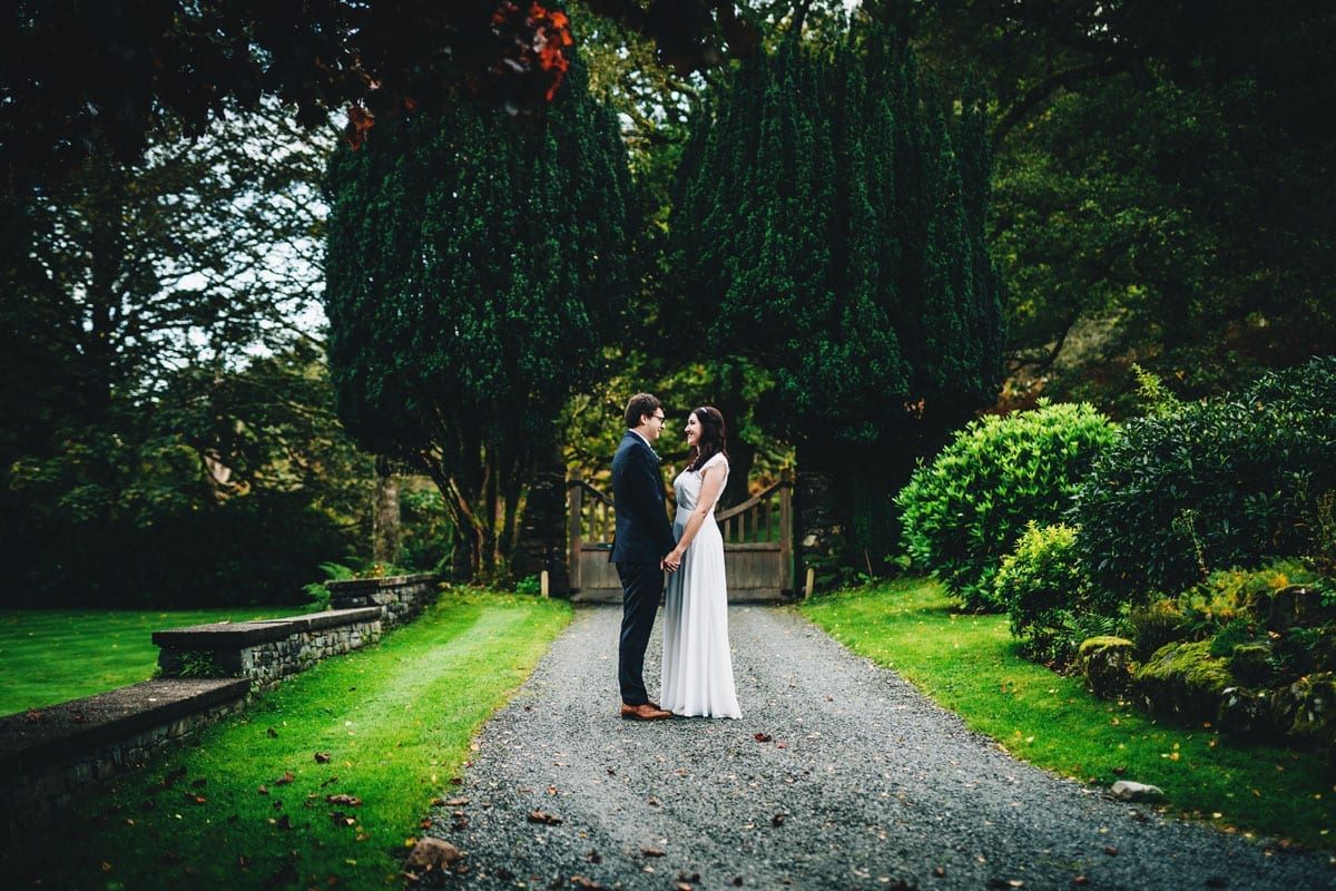 Bride and Groom with yew trees behind them in the driveway of Cote How in the Lakes after their Covid wedding in 2020