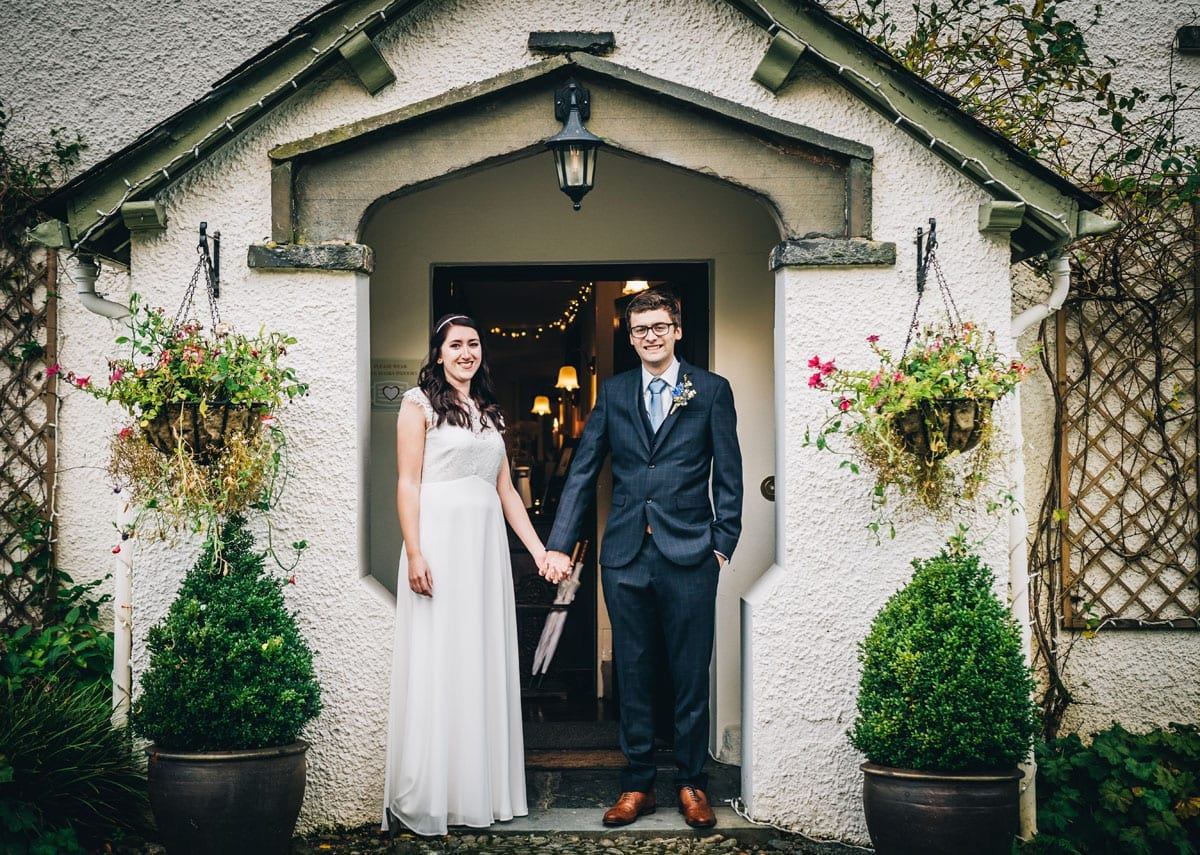 Bride and Groom standing in the Tudor porch at Cote How Lake District Wedding Venue in Rydal