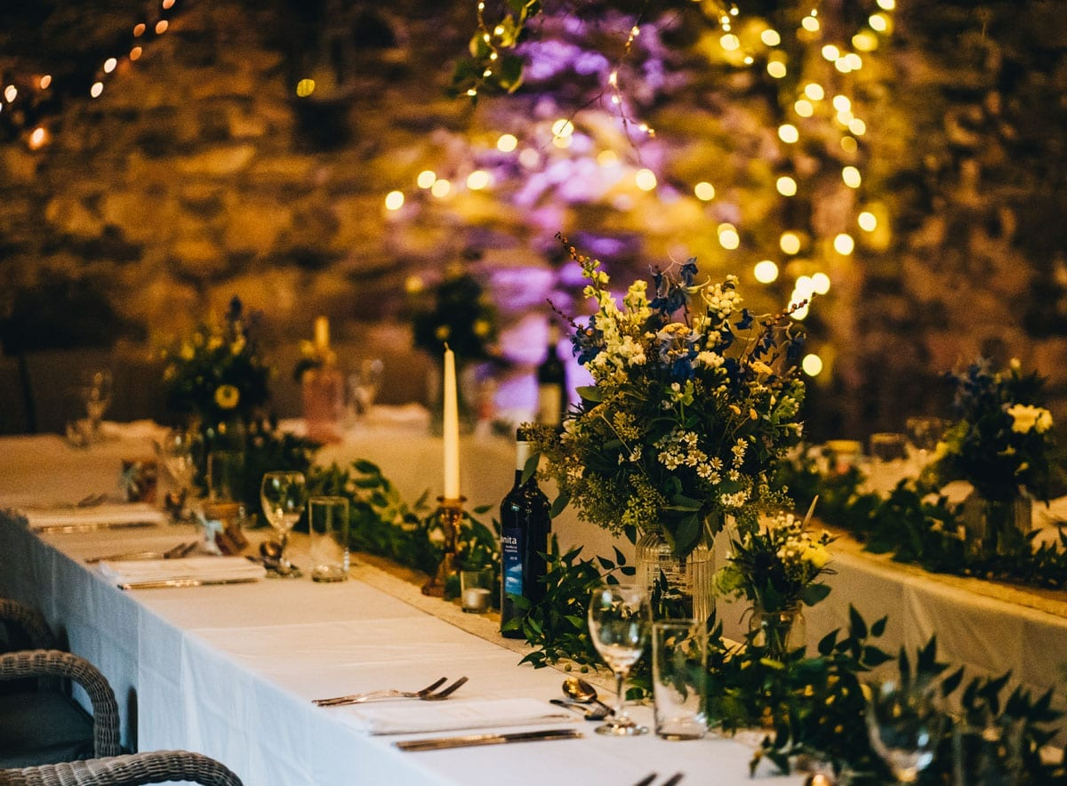Table Setting in a wedding barn with warm glowing candlelight and fairy light tablescape