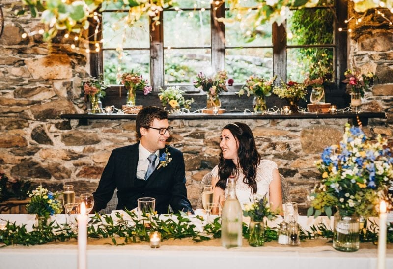 Bride and Groom seated at their wedding breakfast in a slate wedding barn with a window, flowers and soft lighting