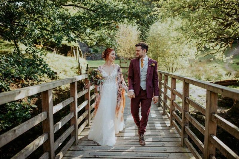 Wedding couple walking over rustic bridge in Rydal